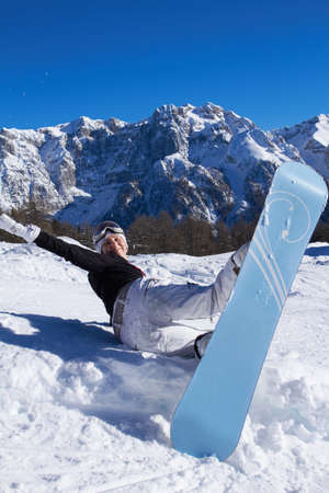 Happy female snowboarder havin fun in mountains photo