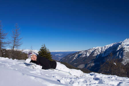 Cute tired snowboarder is resting on her snowboard photo