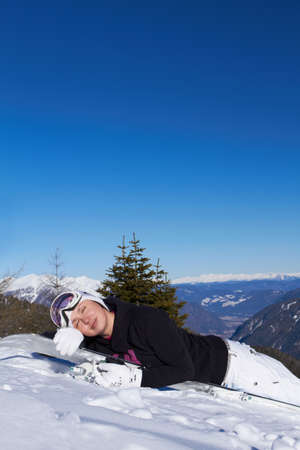 Female snowboarder is sleeping on snowboard photo