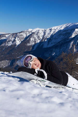 A girl in a ski suit in the mountains in winter laying on snowboard photo