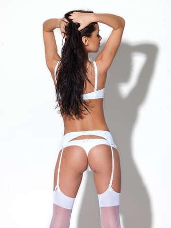 Cute female in white lingerie on white
