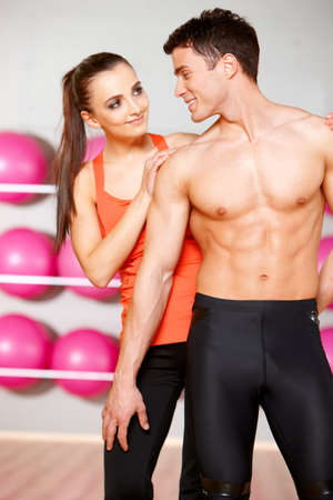 strong girl: Sporty couple exercising at the fitness gym Stock Photo
