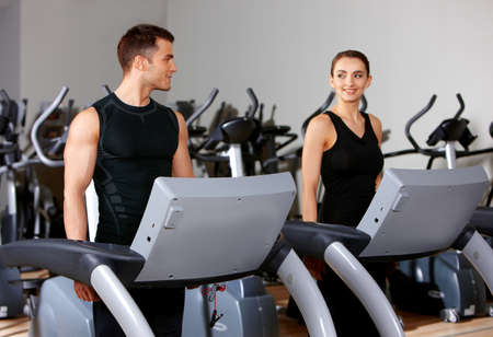 exercise machine: Sporty couple exercising at the fitness gym Stock Photo
