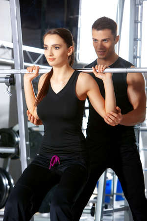 fitness equipment: Sporty couple exercising at the fitness gym Stock Photo