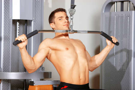 musculoso: Hombre guapo en el gimnasio haciendo ejercicios