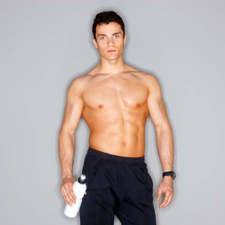 Muscular and tanned male isolated on grey photo