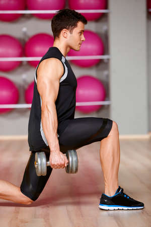 pesas: Hombre guapo en el gimnasio haciendo ejercicios