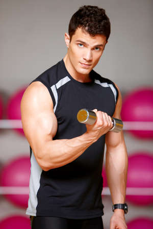 Handsome man at the gym doing exercises Stock Photo - 9796029
