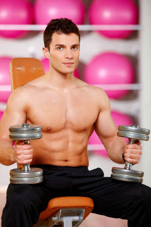 Handsome man at the gym doing exercises Stock Photo - 9796017