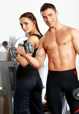 fit on: Sporty couple exercising at the fitness gym Stock Photo