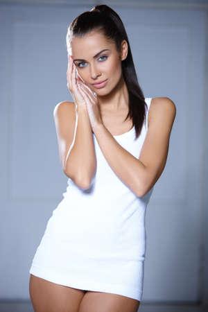 Beautiful young woman standing on grey background Banco de Imagens