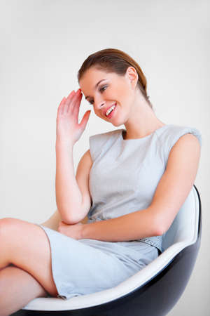 Portrait of a young attractive business woman sitting on chair photo