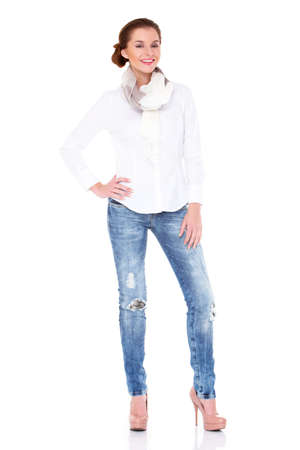 Young sexy brunette woman in white shirt and blue jeans isolated photo
