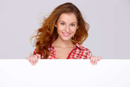 advertisment: Lovely young woman in casual clothing holding empty board