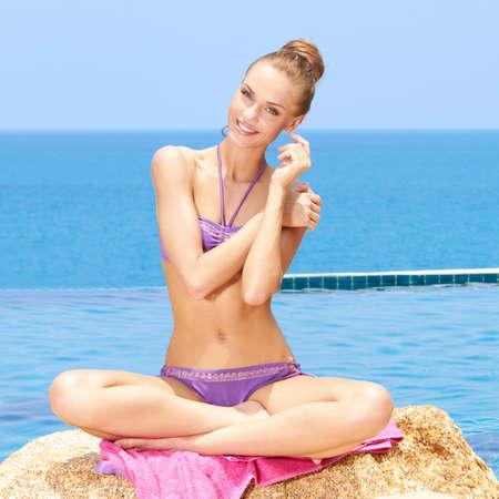 Beautiful woman In a bikini sitting on a rock at the edge of an infinity pool Stock Photo - 13106432