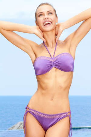 Sexy female in purple bikini with raised arms posing on beach photo