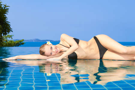 woman bathing: Smiling woman with wet hair laying with her arms on the tiled edge of the pool reflected in the water below Stock Photo