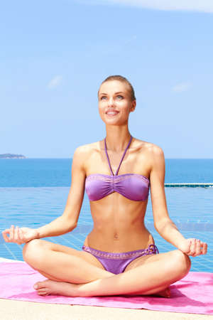 Beautiful woman sitting in yoga position at the edge of pool Stock Photo - 13106663