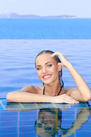 Smiling woman with wet hair standing with her arms on the tiled edge of the pool reflected in the water below Stock Photo - 13106717