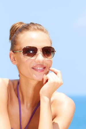 blonde yeux bleus: Jolie jeune femme à la plage avec des lunettes de soleil Banque d'images