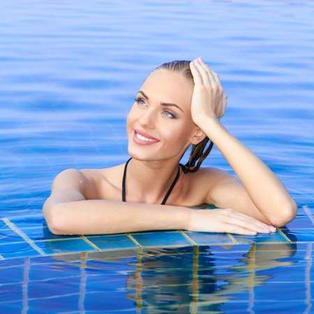 mujer ba�andose: Mujer sonriente con el pelo mojado, con los brazos en el borde de azulejos de la piscina refleja en el agua por debajo de Foto de archivo