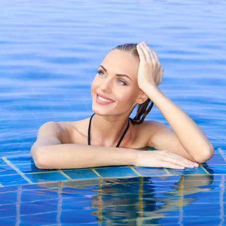 Smiling woman with wet hair standing with her arms on the tiled edge of the pool reflected in the water below