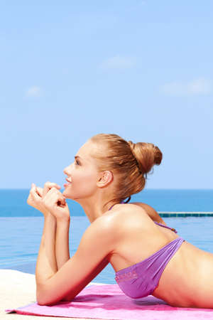 Blond young woman laying next to swimming pool Stock Photo - 13106440