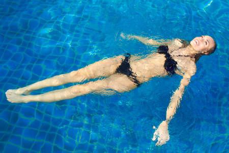 Sonriente mujer hermosa con un bikini acostada de espaldas flotando en una piscina de relax bajo el sol caliente del verano