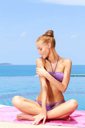 bikini pool: Beautiful woman In a bikini sitting on towel at the edge of an infinity pool