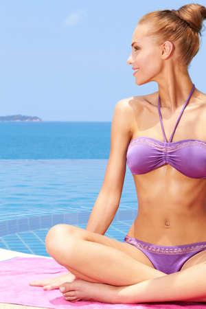 Beautiful woman In a bikini sitting on towel at the edge of an infinity pool photo