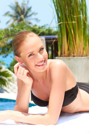 Close up of beautiful woman lying next to swimming pool photo