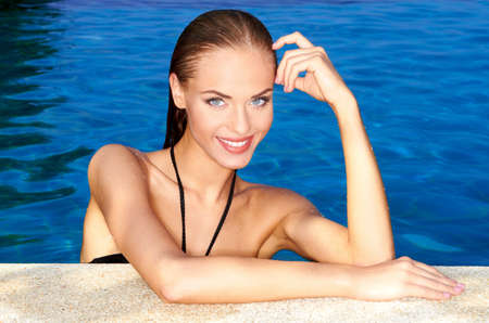 smiling sun: Sexy smiling woman at the edge of swimming pool