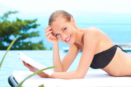 Cute woman reading a book next to swimming pool photo