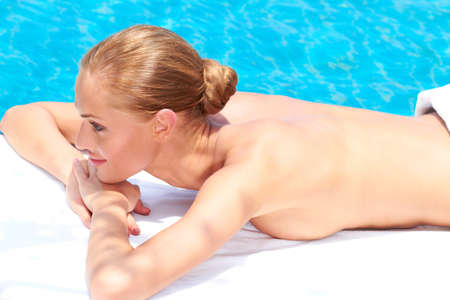 Woman during spa treatment next to swimming pool photo