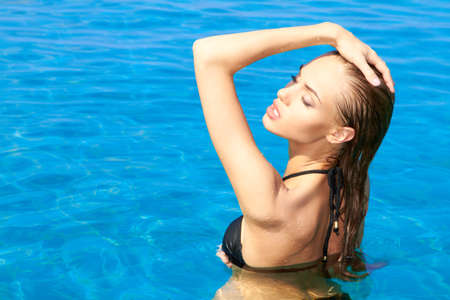 exotic woman: Sensual and sexy woman standing in swimming pool Stock Photo