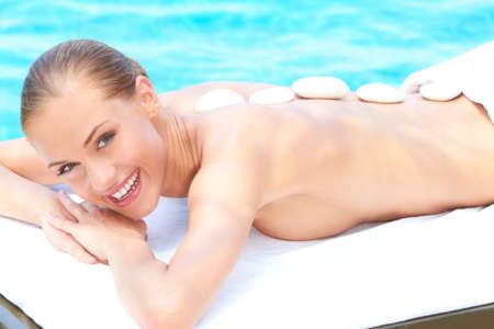 Relaxed woman taking spa treatment close to swimming pool photo