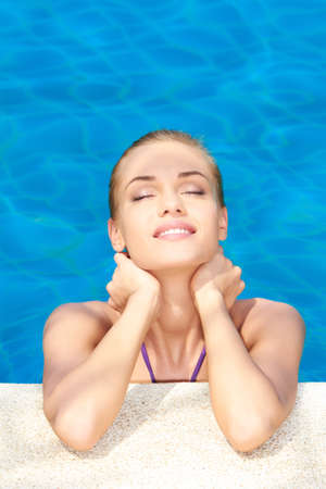 Dreaming woman with eyes closed in swimming pool