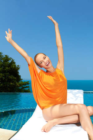 Happy woman having fun next to swimming pool photo