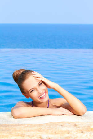 Close up of cute girl in infinity pool with copy space photo