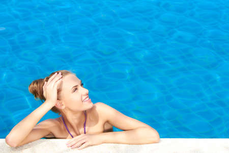 Cute girl in swimming pool looking at copy space photo