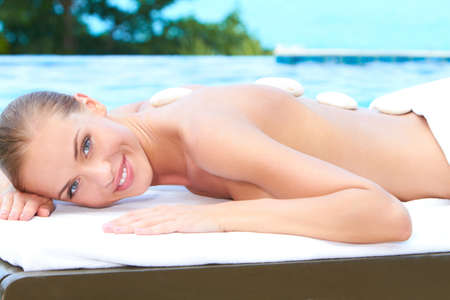 spa stones: Beautiful woman lying on spa bed at exotic outdoor