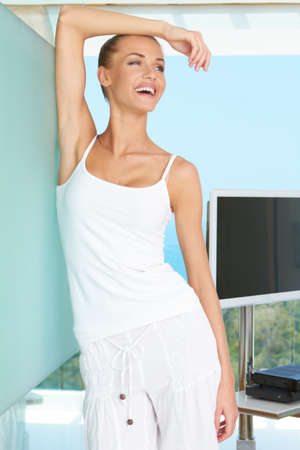 Woman standing laughing in casual white outfit in a modern glass fronted living room with a view of the ocean Stock Photo - 13202090