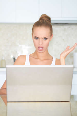consternation: Woman seated at a table looking at her laptop screen in consternation and horror