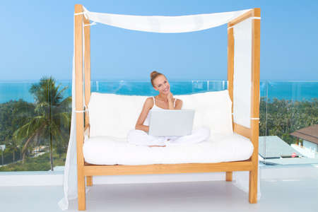 Fresh bright portrait of a woman sitting cross legged on a canopied seat with her laptop backed by a large window overlooking the ocean Stock Photo - 13202195
