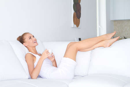 recline: Beautiful elegant woman barefoot in a white dress reclining on a sofa drinking coffee