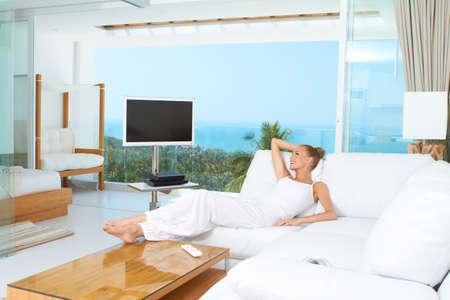 Woman relaxing on a sofa with her bare feet on the coffee table in spacious bright white living-room with glass window overlooking the ocean photo