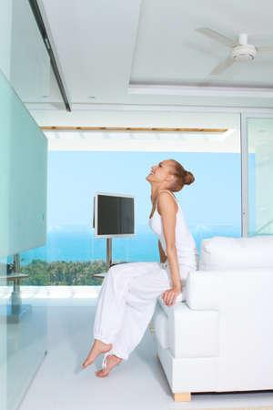 baggy: Graceful woman in white baggy slacks sitting barefoot on the edge of a white sofa in a modern glass fronted living-room with ocean view