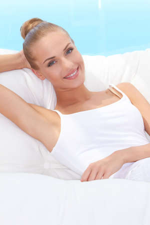 Closeup of a lively laughing beautiful woman reclining back on a white sofa against blue sky Stock Photo - 13202037