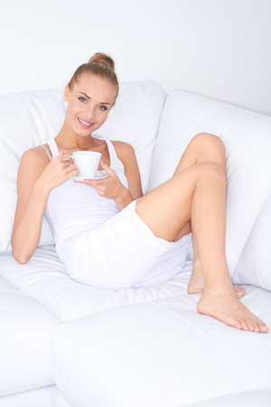 drinking tea: Beautiful elegant woman barefoot in a white dress reclining on a sofa drinking coffee
