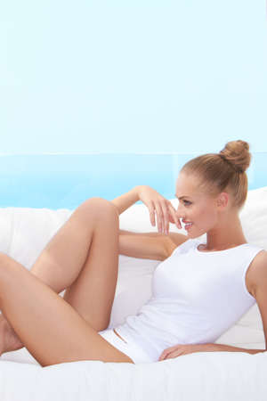 tight fitting: Laughing woman in panties and a tight fitting white shirt lying on her stomach on a bench with cushions looking back over her shoulder Stock Photo